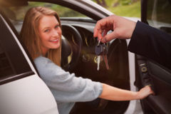 Composite image of couple receiving car keys by a dealer. Couple receiving car keys by a dealer against portrait of young women in car Stock Photography