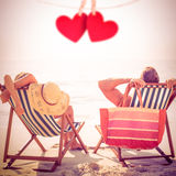 Composite image of couple relaxing on the beach Royalty Free Stock Photography