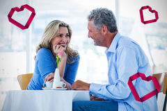 Composite image of couple in restaurant and hearts 3d Stock Photos