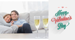 Composite image of couple resting on a couch with flutes of champagne. Couple resting on a couch with flutes of champagne against valentines day greeting Royalty Free Stock Image