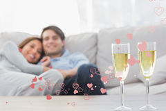 Composite image of couple resting on a couch with flutes of champagne. Couple resting on a couch with flutes of champagne against valentines heart design Stock Image