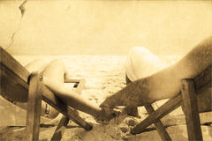 Composite image of couple resting on deck chairs Stock Photos