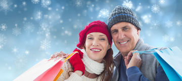 Composite image of couple with shopping bags. Couple with shopping bags against snowflakes over blue background Royalty Free Stock Photo
