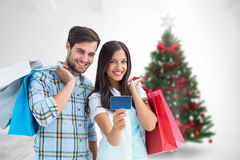 Composite image of couple with shopping bags and credit card Royalty Free Stock Image