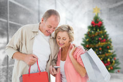 Composite image of couple with shopping bags and smartphone. Couple with shopping bags and smartphone against home with christmas tree Stock Photos