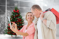 Composite image of couple with shopping bags and tablet Stock Image