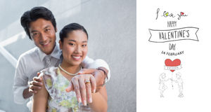 Composite image of couple showing engagement ring on womans finger Stock Photo