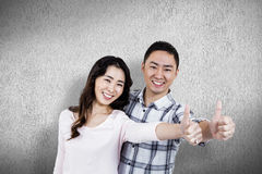Composite image of couple showing thumbs up while standing. Couple showing thumbs up while standing  against white and grey background Royalty Free Stock Images