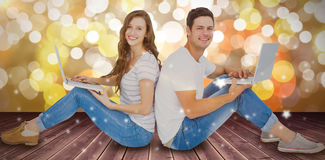 Composite image of couple sitting on floor back to back using laptop Royalty Free Stock Photo