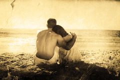 Composite image of couple sitting on the sand watching the sea Stock Image