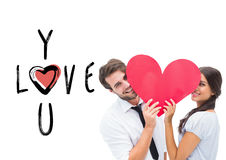 Composite image of couple smiling at camera holding a heart Stock Photo