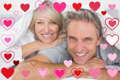Composite image of couple smiling under the covers Royalty Free Stock Photography
