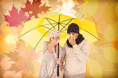 Composite image of couple sneezing in tissue while standing under umbrella Stock Photo