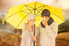 Composite image of couple sneezing in tissue while standing under umbrella. Couple sneezing in tissue while standing under umbrella against country scene Royalty Free Stock Photography