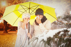Composite image of couple sneezing in tissue while standing under umbrella Royalty Free Stock Photo