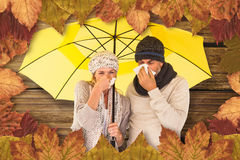 Composite image of couple sneezing in tissue while standing under umbrella Stock Photography