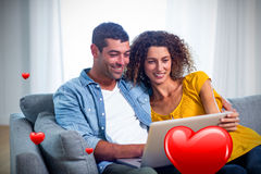 Composite image of couple on sofa and valentines hearts 3d Royalty Free Stock Images