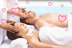 Composite image of couple in spa and valentines hearts 3d Royalty Free Stock Photo