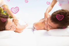 Composite image of couple in spa and valentines hearts 3d Stock Image