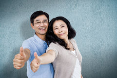 Composite image of couple standing together with thumbs up Stock Images
