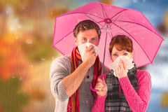 Composite image of couple standing underneath an umbrella Royalty Free Stock Photography