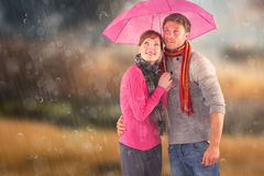Composite image of couple standing underneath an umbrella Royalty Free Stock Images