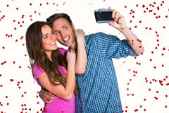 Composite image of couple taking selfie with digital camera. Couple taking selfie with digital camera against red love hearts stock images