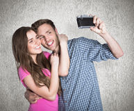Composite image of couple taking selfie with digital camera Stock Images