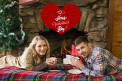 Composite image of couple with tea cups in front of lit fireplace. Couple with tea cups in front of lit fireplace against cute valentines message Royalty Free Stock Images