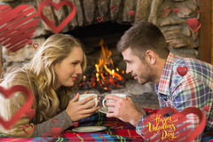 Composite image of couple with tea cups in front of lit fireplace. Couple with tea cups in front of lit fireplace against happy valentines day Royalty Free Stock Photography