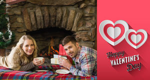 Composite image of couple with tea cups in front of lit fireplace. Couple with tea cups in front of lit fireplace against happy valentines day Stock Photo