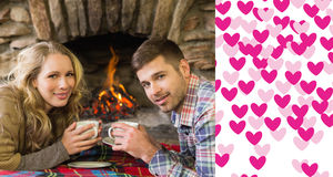 Composite image of couple with tea cups in front of lit fireplace. Couple with tea cups in front of lit fireplace against valentines day pattern Stock Photo