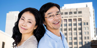 Composite image of couple with their backs to each other. Couple with their backs to each other against low angle view of city buildings stock photo