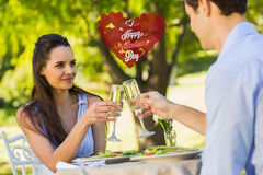 Composite image of couple toasting champagne flutes at an outdoor café. Couple toasting champagne flutes at an outdoor café against cute valentines message Royalty Free Stock Images