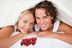 Composite image of couple under a duvet Stock Images