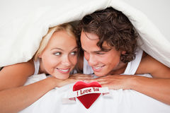 Composite image of couple under a duvet with a knowing smile Royalty Free Stock Image