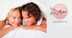 Composite image of couple under a duvet with a knowing smile Stock Images