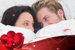Composite image of couple under the duvet looking at each other Stock Photo