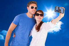 Composite image of couple using camera for picture Stock Photos
