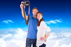 Composite image of couple using camera for picture Stock Image