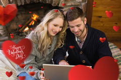 Composite image of couple using laptop in front of lit fireplace Stock Photography