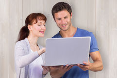 Composite image of couple using a laptop together Royalty Free Stock Photos
