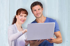 Composite image of couple using a laptop together Royalty Free Stock Photography