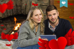 Composite image of couple using tablet pc in front of lit fireplace. Couple using tablet PC in front of lit fireplace against heart label Royalty Free Stock Photo