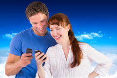 Composite image of couple using their mobile phones Stock Photo