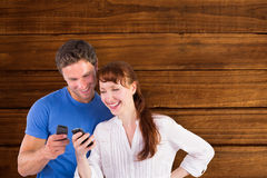 Composite image of couple using their mobile phones Royalty Free Stock Photo