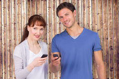 Composite image of couple using their mobile phones Royalty Free Stock Images