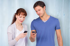Composite image of couple using their mobile phones Royalty Free Stock Image