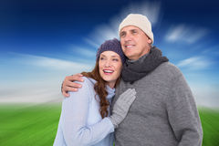 Composite image of couple in warm clothing embracing Stock Image