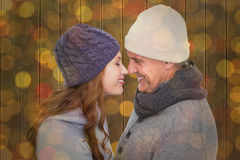 Composite image of couple in warm clothing facing each other Stock Photography